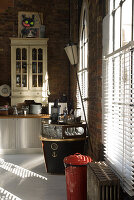 Vintage-style collector's items in loft kitchen lit from the side through large windows