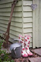 Wellies, watering can and garden tools next to shed
