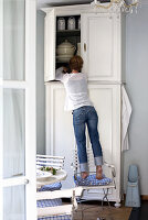 Woman standing on English garden chair putting away crockery in white, country house cupboard