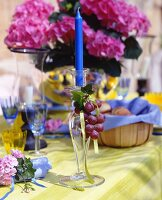 Summery set table decorated with grapes and hydrangeas