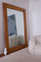 Large, wood-framed mirror showing reflection of modern painting and fluffy armchair in period apartment