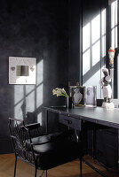 Desk below sunny window in corner of room with postmodern decor and anthracite walls