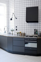 Kitchen counter with black base cabinets against walls tiled from floor to ceiling