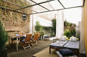 Mediterranean patio area with bed, table, chairs and an elegant mosquito net