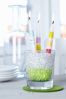 Candles decorated with stripes of tape in drinking glass filled with decorative pebbles