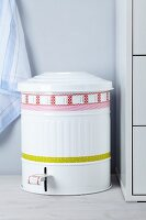 Vintage-style metal pedal bin decorated with patterned tape