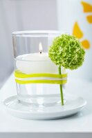 Floating candle in glass with flower held on by rubber band