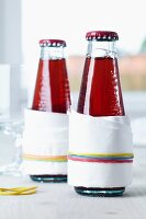 Drip catchers on drinks bottles; paper napkins held in place with rubber bands