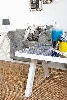 White coffee table with mosaic tiles on sisal rug and pale grey cord armchair with scatter cushion
