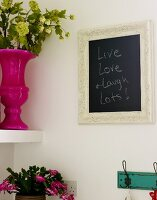 Framed blackboard hanging on a wall next to a shelf with a potted plant and flower vase