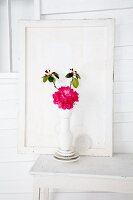 Rhododendron (variety: 'Abendsonne') in white vase on table in front of wooden panel