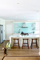 Bright country-house kitchen with pastel turquoise back wall and rustic wooden stools at breakfast bar