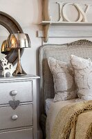 Romantic decor in silver and natural shades at head of country-house-style bed