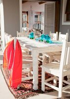 Red towel on a white, lacquered wooden chair and table on a terrace