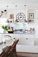 White, open-plan kitchen with pendant lamps, wall clock, rustic dining table and wicker chairs