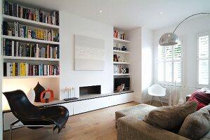 modernes wohnzimmer mit eingebautem b cherregal neben offenem kamin und klassiker st hlen bild. Black Bedroom Furniture Sets. Home Design Ideas