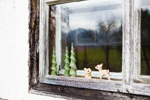 Small figurines in old, wooden farmhouse window