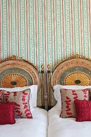 Twin beds with elaborately carved and painted headboards against striped wallpaper
