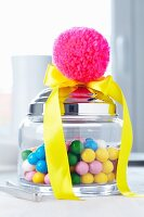 Jar of sweets decorated with yellow satin ribbon & pink pompom