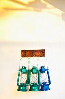Colourful vintage lanterns hanging on coat rack