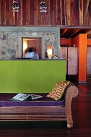 Contrast in colors in the lobby of an eco-lodge; wall paneling and wooden bench made from precious wood from Africa