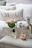 Roses, perfume and silver vase on bedside table