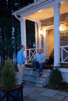 Two men drink the front of the lighted porch of a house