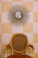 Rococo chair with mesh on back of wall decorations on wallpapered wall with white yellow plaid