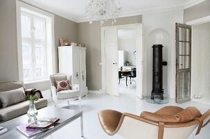 Different armchairs in renovated interior with walls painted pale grey and round iron stove in niche