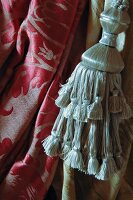 Silver grey tassel with red and pink panne velvet in background