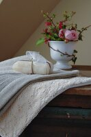 Romantic, natural spa utensils - packaged soap on towel and lace cloth with china goblet of roses in background
