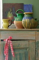 Painted ceramic vessels on vintage wooden cabinet