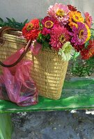 Colourful bouquet in rattan shopping bag on vintage wooden bench