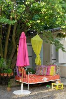 A metal daybed in the garden next to a closed, pink sunshade and a yellow canopy hanging from a tree