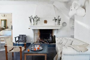 Soot-blackened fireplace, table, sofa, chairs and animal head sculpture on wall in renovated country house