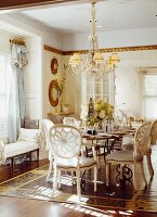 Vintage-style dining room - chairs with latticed backs around set table below chandelier with fabric lampshades