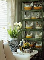 Bouquet of white tulips in ceramic vase on tray in front of china hen figurines on cage-like shelving