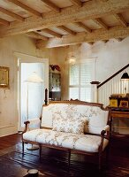 Antique couch with floral upholstery in interior with rustic, wood-beamed ceiling