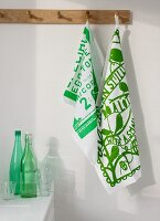 Printed, green and white dish cloths on wall hooks above a kitchen counter with bottles