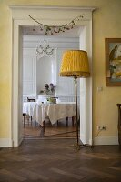 View into a dining room with a round table, in the foreground an old floor lamp with a fabric shade