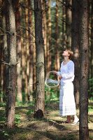 Young woman in romantic, white summer clothing with wicker basket in pine forest