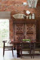 Dark wooden dining table and chairs in front of antique, carved cabinet and exposed brick wall