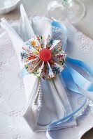 Colourful paper rosette with red button on pale blue ribbon as napkin ring tying napkin and cutlery