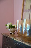 Glass vases and bowl of flowers on vintage chest of drawers