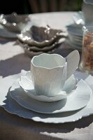 White, designer china teacup with matching saucer and plate