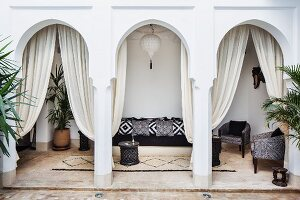 View from courtyard of black and white sofa and armchairs in Oriental arcade with draped curtains