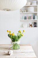 Bouquet of ranunculus in glass vase with decorative cord on wooden table; detail of pendant lamp in foreground and shelving in niche in background