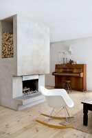 Eames rocking chair in front of concrete chimney breast with open fireplace and niche for firewood; piano with swivel stool in background