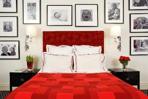 Red double bed framed by large collection of black and white photographs