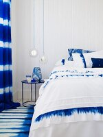 Blue and white bedroom with double bed, bedside table, rug & curtains